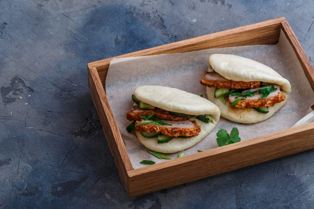 Two steamed buns with pork belly in a box, copy space